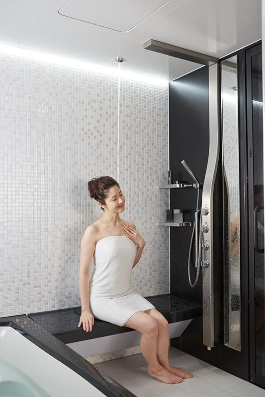 女性が浴室の天井から落ちる打たせ湯『アクアタワー』にかかって、リラックスしている