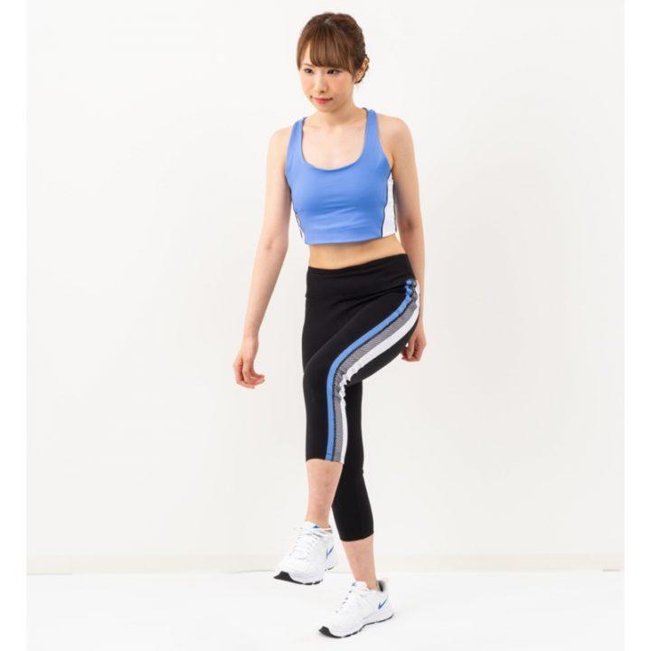 片脚をあげるトレーニングウエア姿の女性