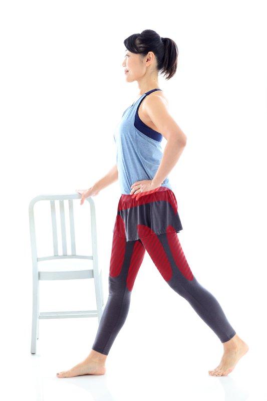 スの背に右手を置き左手を腰に当て、右足を前にして足を大きく前後に開いて立つ