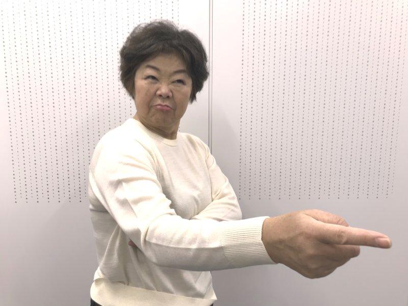白のニットを着て指差すオバ記者