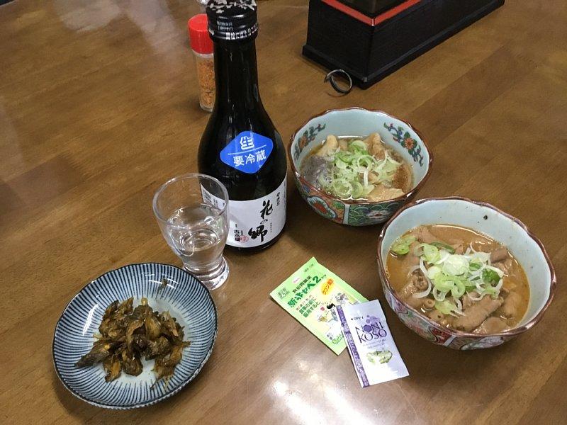 『かまたや』の牛すじの煮込み、もつ煮込み、日本酒が並べられている