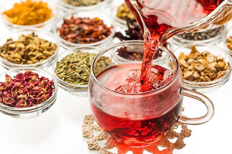 ガラスのカップに赤いハーブティーが注がれている。その後ろには様々な茶葉が並んでいる