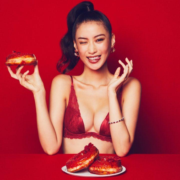 赤い下着姿でドーナツをもち微笑む女性