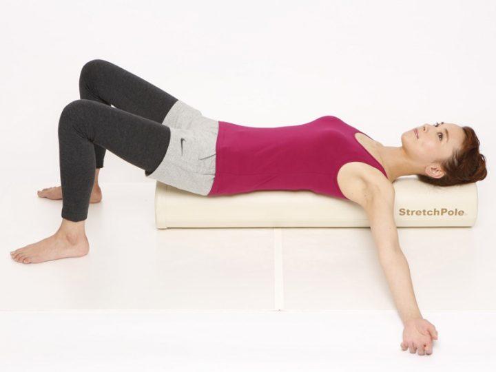 ストレッチポールに寝転ぶ女性