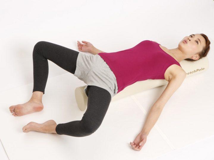 ストレッチポールの上に寝転び脚を開く女性