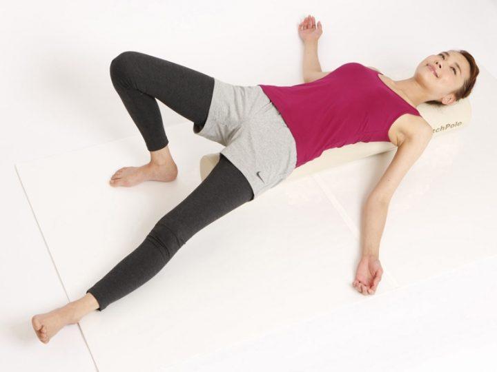 ストレッチポールの上に寝転び片脚を伸ばす女性