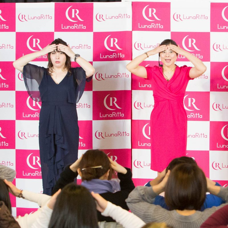 顔ヨガを見せる顔ヨガ講師の間々田佳子さんと司会者の女性