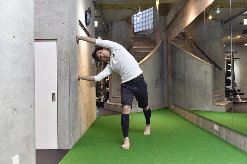 東田雄輔さんによる「お手軽1分ストレッチ」のやり方。体を傾けて両手を壁にしてキープ