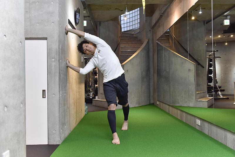 東田雄輔さんによる「お手軽1分ストレッチ」のやり方。体を傾けて両手を壁に。