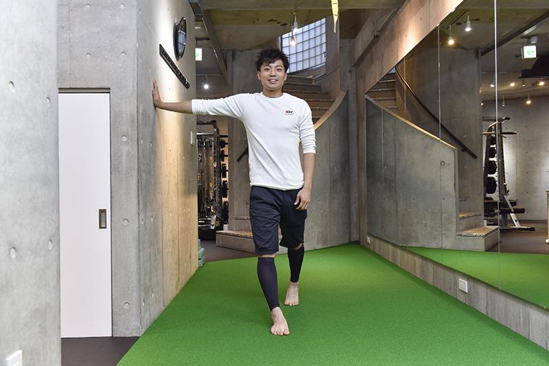 東田雄輔さんによる「お手軽1分ストレッチ」のやり方。右手で壁を押している