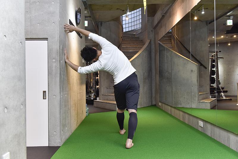 東田雄輔さんによる「お手軽1分ストレッチ」のやり方。体を傾けて両手を壁に。後ろから見た体勢