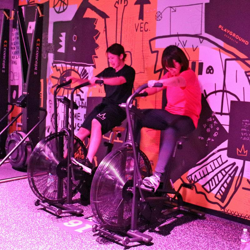 自転車を漕ぐマシンを体験するライターF