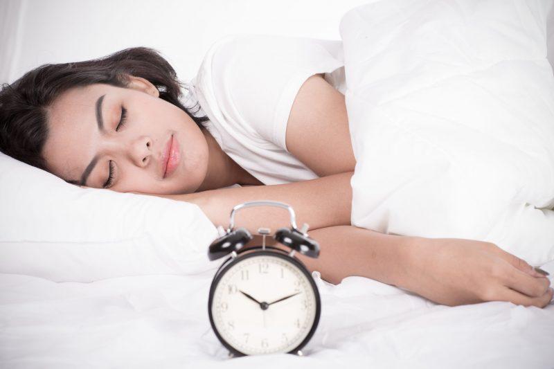 10時をさす時計の前でぐっすり眠る女性