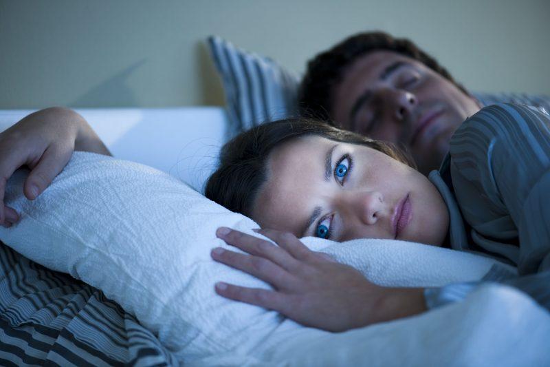 薄暗い部屋で布団の中に入っているが目を開けている女性と、ぐっすり眠る男性