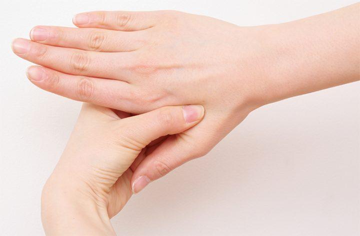 右手の親指と人さし指の間を左手の親指で押さえている