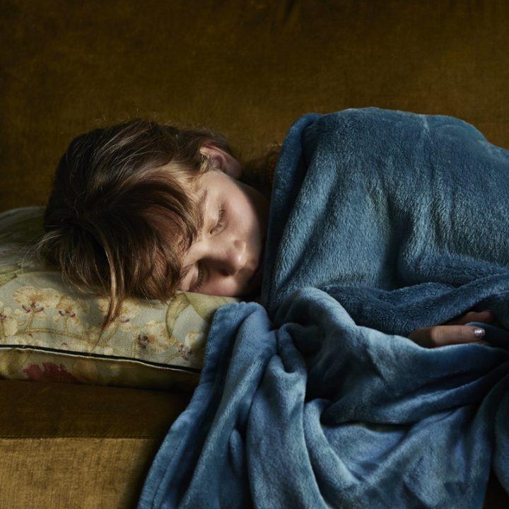 毛布をかぶって寝ている少女