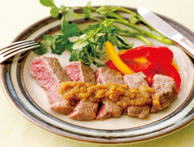 オニオンマリネステーキがパプリカやルッコラと一緒に皿に盛りつけられている