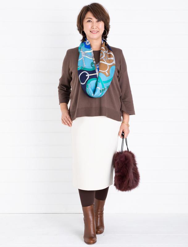 茶色のニットにスカート、茶色のブーツをはいた女性。ターコイズブルーのスカーフが目立つ