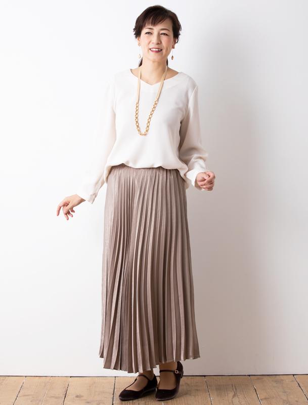 白のVネックニットに金の太いチェーンネックレス、濃いベージュのプリーツスカートを着た女性
