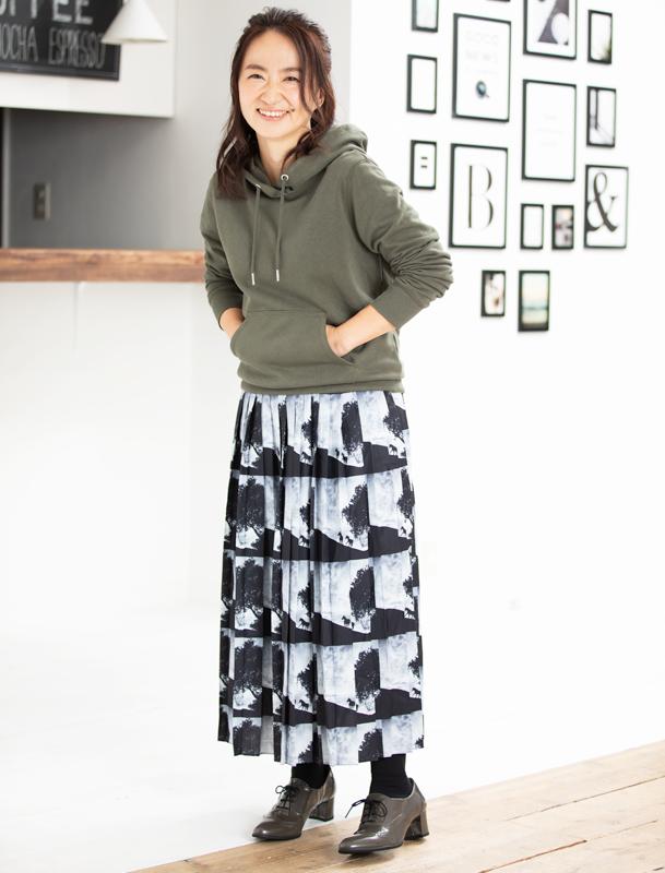カーキのパーカーに、黒地に白い写真がプリントされたロングスカートを着た女性