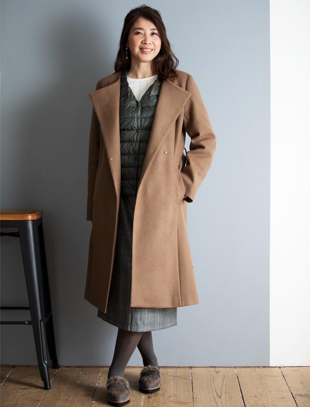 ブラウンのロングコートの下に薄手のダウンを着た女性