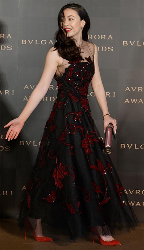黒地に大ぶりの赤い花が描かれたロングドレスをまとったエレナ・アレジ・後藤