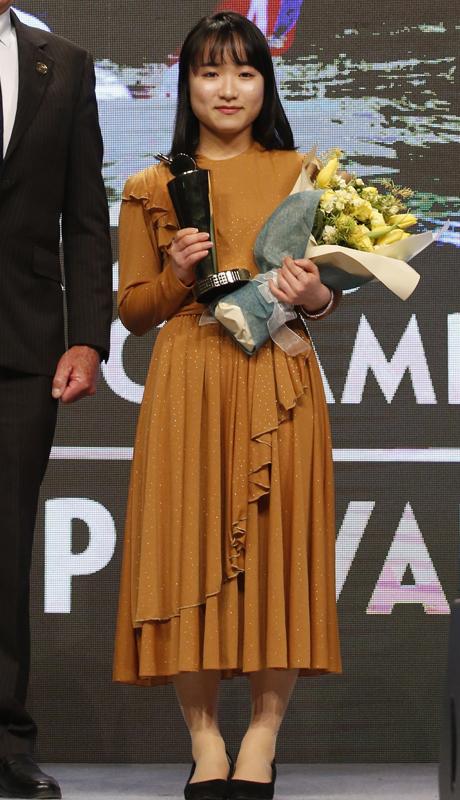 肩からスカートの裾にかけてヒラヒラが付いたキャラメル色のラメ入りドレスを着た伊藤美誠選手