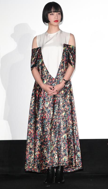 白いノースリーブに、深いVラインが入ったオフショルダーの花柄ロングドレスをまとった小松菜奈