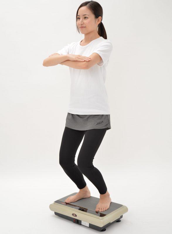 スタイリッシュジャパンのスリミング振動ステッパーに女性が乗って膝を曲げ手を組んでいる