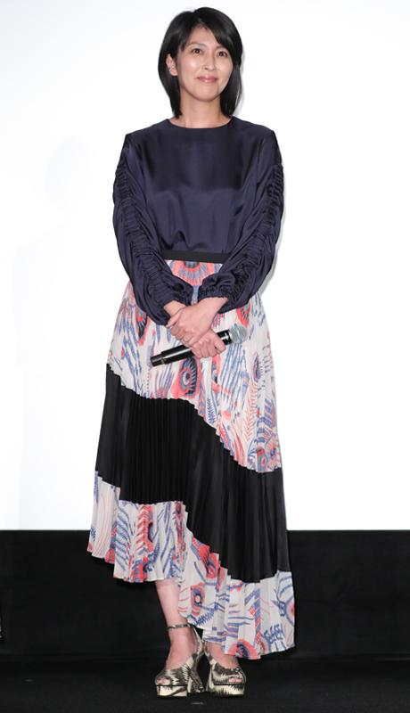 ネイビーのサテントップスに、異素材を組み合わせたアシンメトリーのロングスカートをはいた松たか子