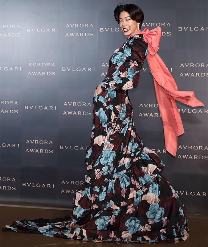 黒地にくすんだ青や錆色の花柄が描かれた超ロングドレスに、首に大きなピンクのリボンをつけた森星