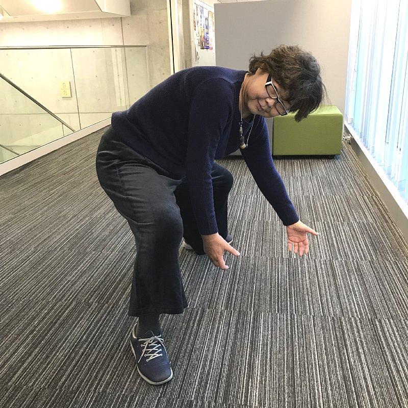 段ボールを得意げに持ち上げる様子を再現するオバ記者