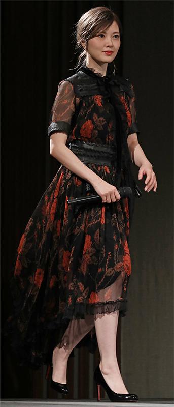 黒地に赤い花が描かれたシフォンドレス姿の白石麻衣