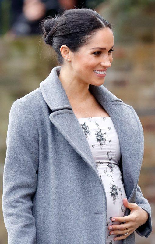 白いぴったりしたトップスにグレーのコートを羽織ったメーガン妃が左手でやさしくお腹に触れている
