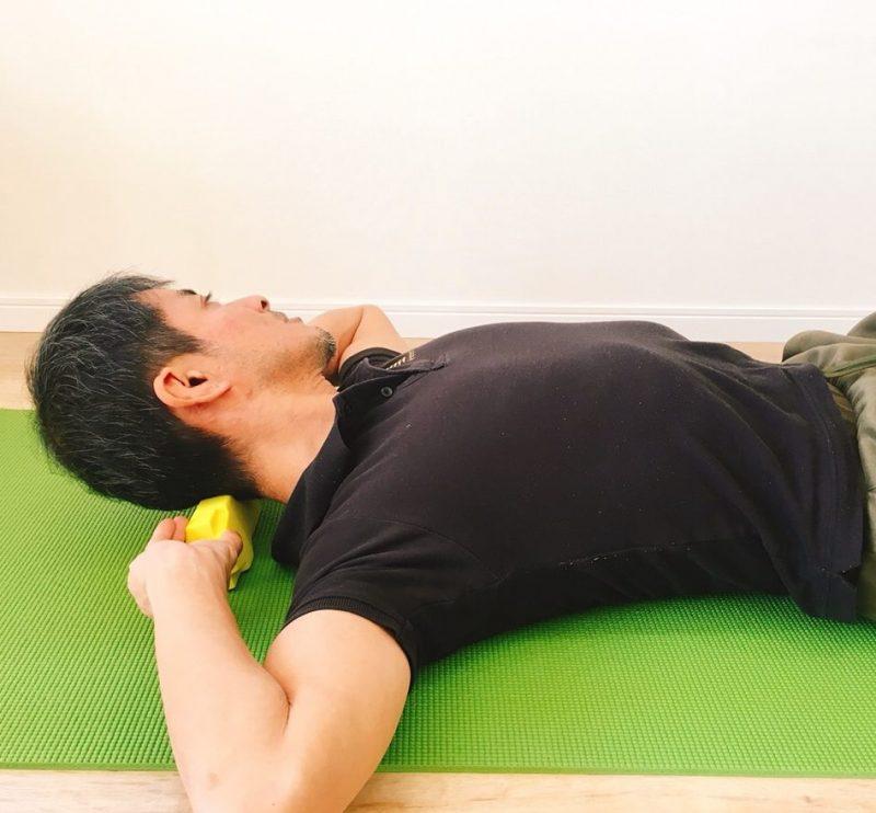 仙骨枕を後頭部に当てて寝転がって体操する男性