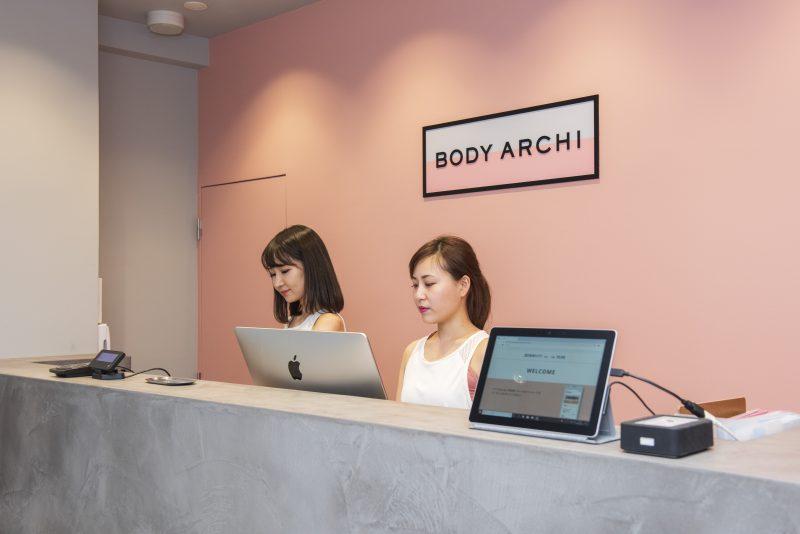 「BODY ARCHI」受付に女性が2人座っている