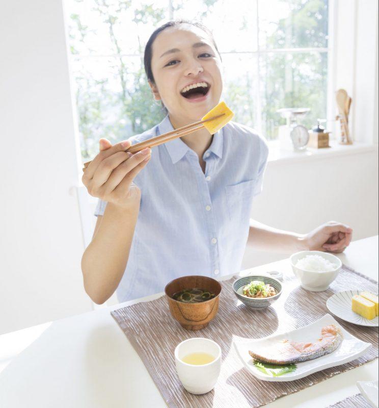 女性が朝食を食べているところ。卵焼きを手に笑顔