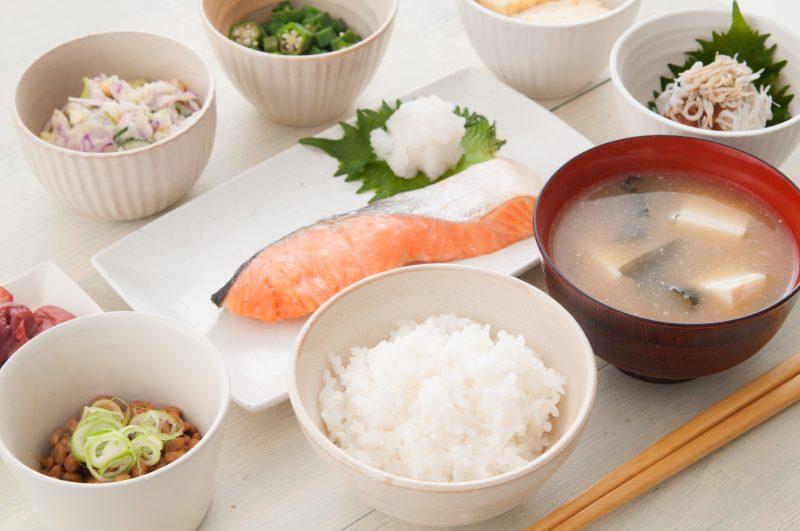 和朝食の写真。ご飯、豆腐の味噌汁、焼き鮭、納豆などがならんでいる