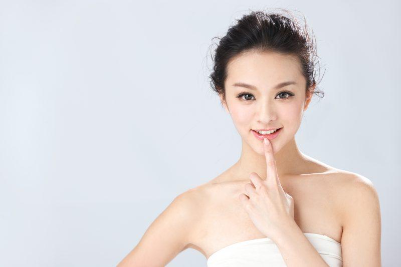 ファンデーションをきっちりした女性が口元に人さし指を当てて微笑んでいる