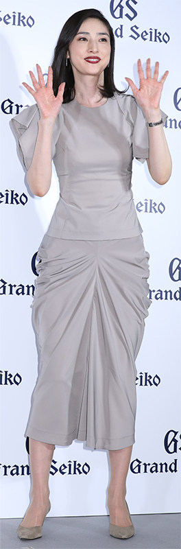 グレーのツーピースドレスを着た天海祐希が両手で手を振っている