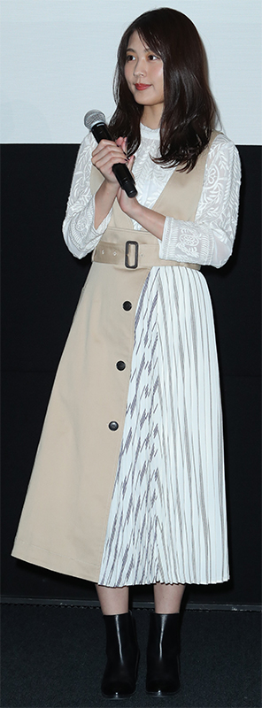 白とストライプ、ベージュの異素材デザインワンピースを着た有村架純がマイクを手に持っている