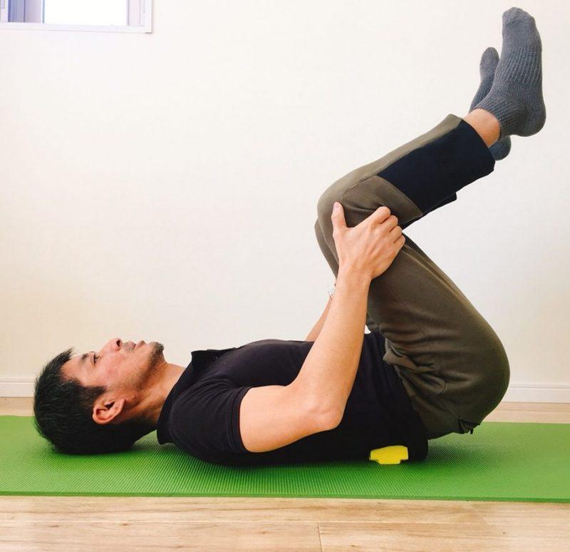 仙骨枕を腰の下に置き上に寝転がり足を上げて体操する男性