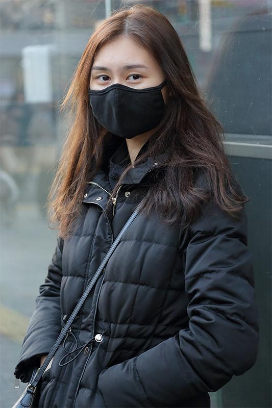 黒いマスクに黒いダウンジャケット姿の女性が街角にたたずんでいる