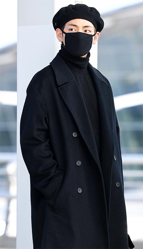 黒いマスクに黒いタートルネックセーター、黒いコート姿のV