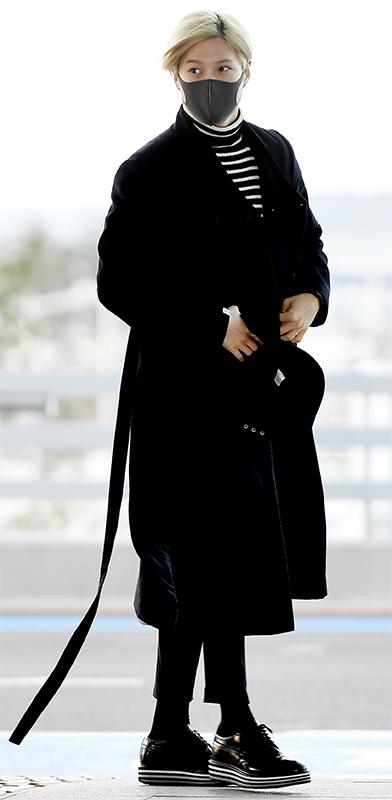 黒マスクに黒いコート、短めの黒いパンツに黒いスニーカーを合わせている