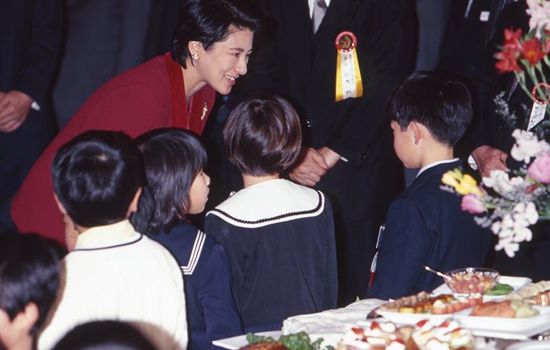 数名の子供たちに自らお声がけをされる雅子さま。赤いスーツをお召しに