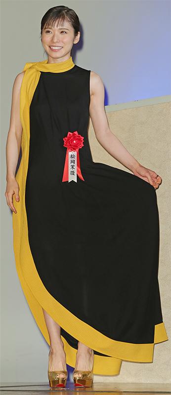 黒のロングワンピースにマスタードカラーの襟元からの太い縁取りのついたドレスを着た松岡茉優