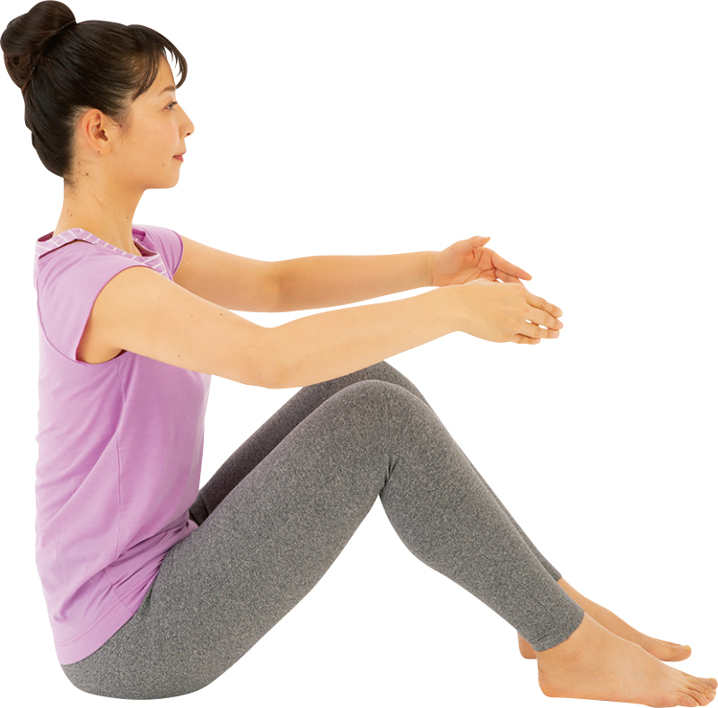 足を立てて座り、肘をかるく曲げて息を吸っている女性