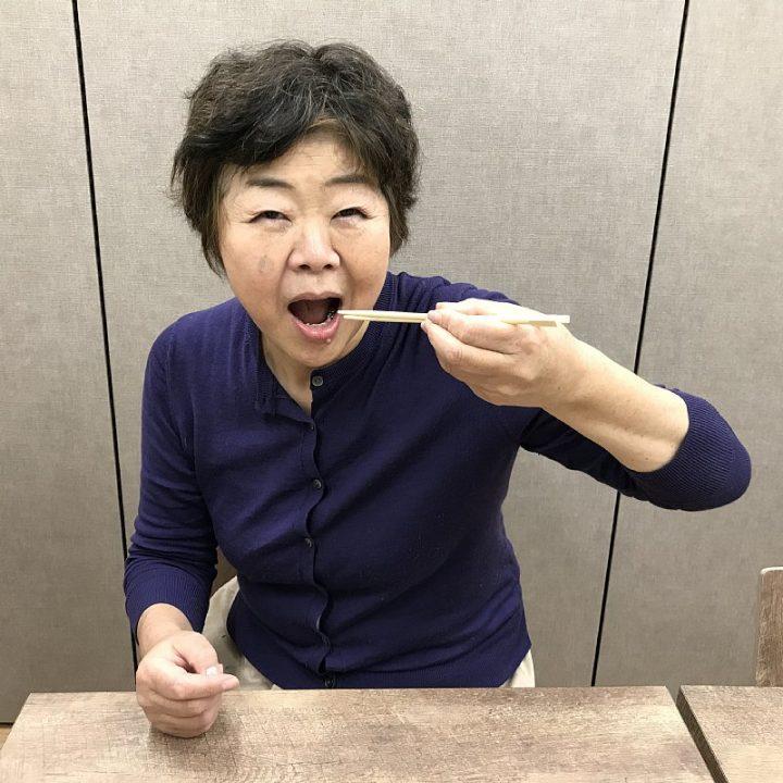 左手で箸を使うオバ記者