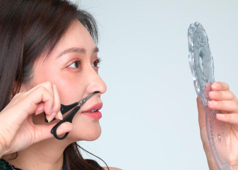 鏡を見ながら綿棒を鼻に入れている